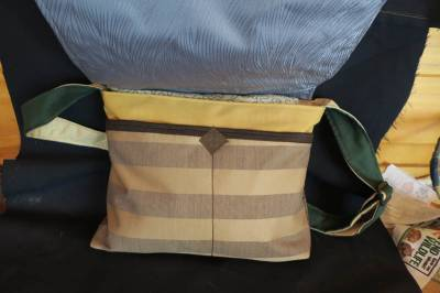 comes with 2 smaller pockets under the flap, a zip to the main compartment and adjustable strap and its all lined.